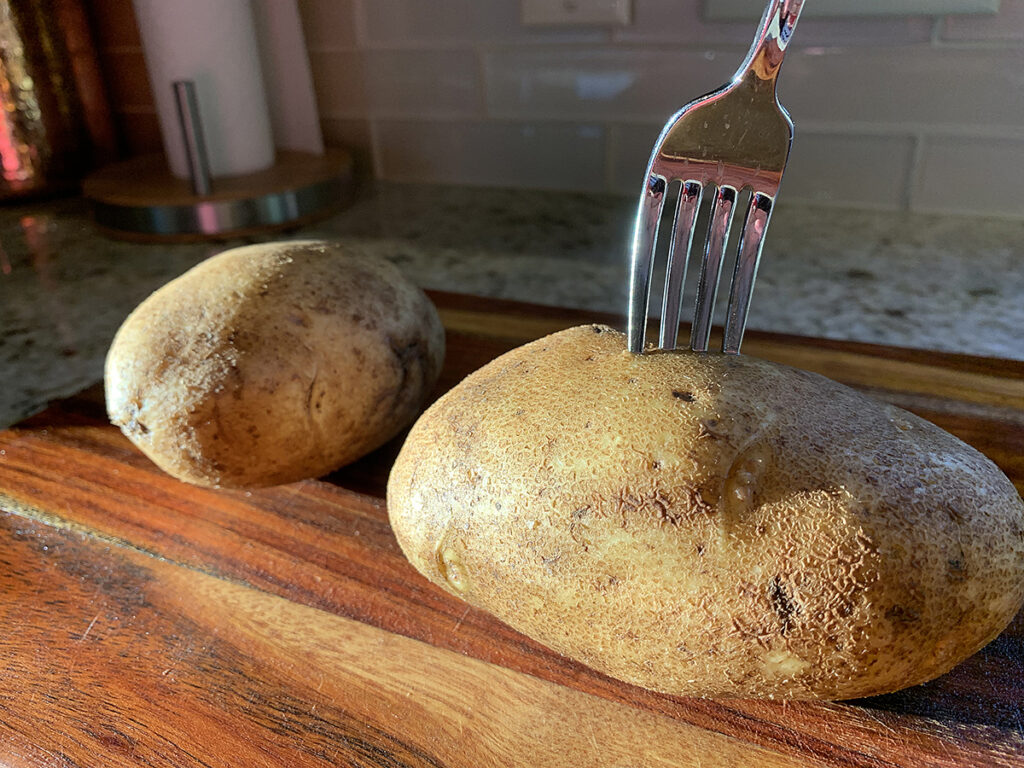 Two baked potatoes on a wood cutting board. One has a fork pierced through it.