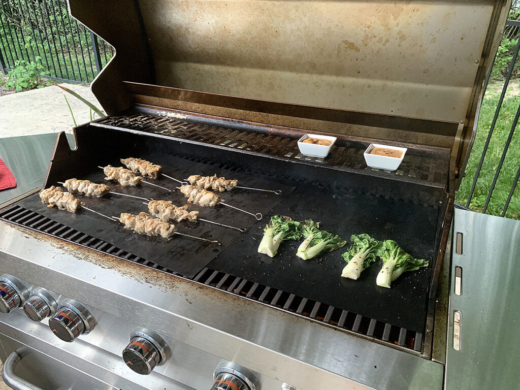 Eight chicken skewers, four spit short bok choys cooking on an outdoor grill.