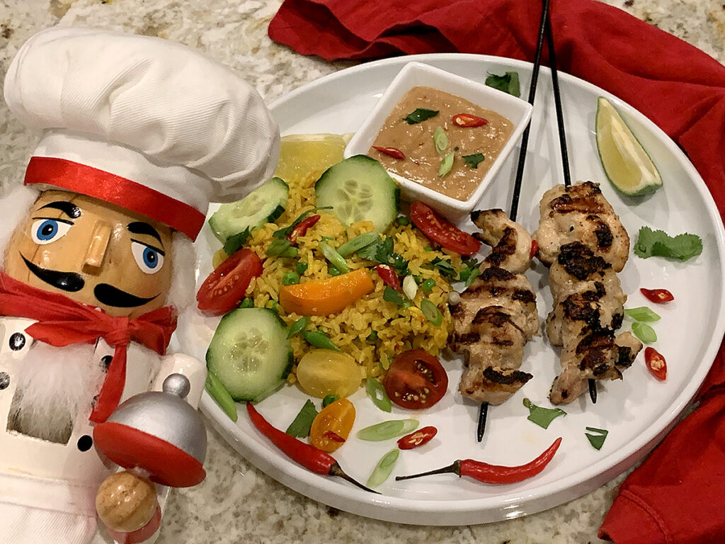 Two skewers of charred, grilled chicken, yellow rice with cucumber, tomato and orange bell pepper slices, on a round white plate along with a tan sauce in a square white ramekin and all garnished with lime wedges, red Thai chilies and cilantro. There's a nutcracker in the foreground who looks like a chef.