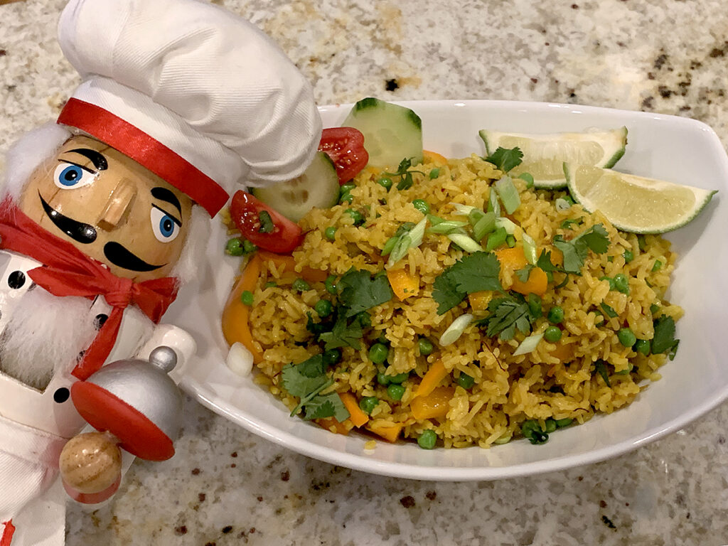 White oval bowl with yellow rice, garnished with lime wedges, cucumber slices, tomato slices, orange bell peppers, chopped green onions and cilantro. There's a nutcracker in the foreground who looks like a chef.