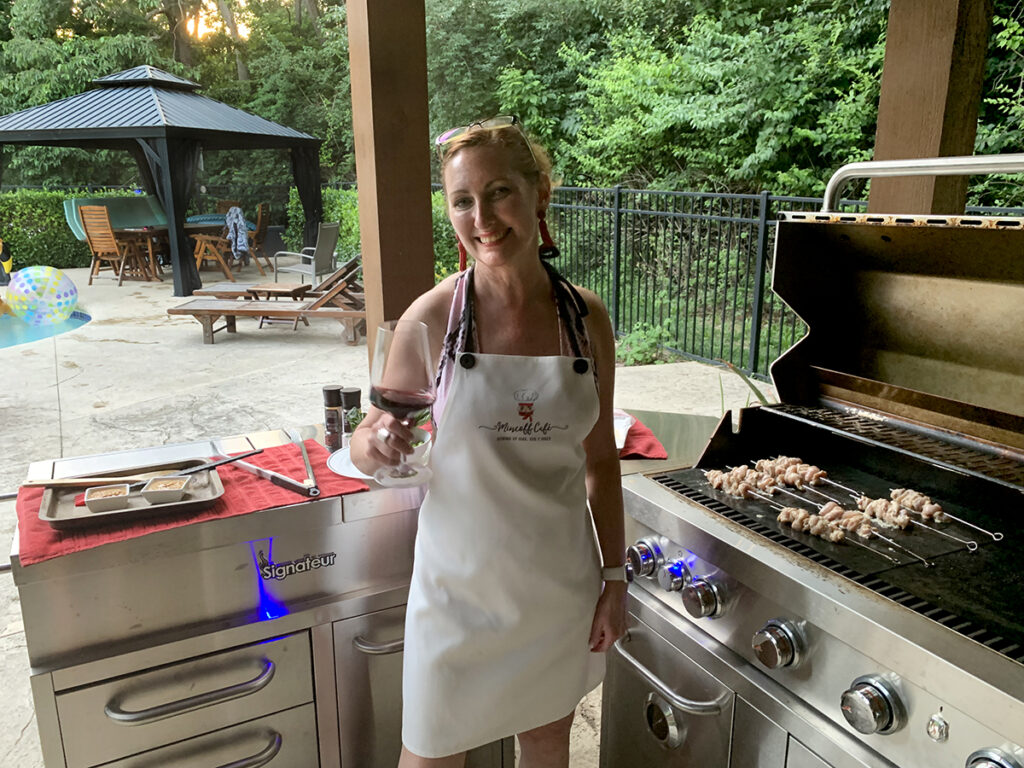 White woman with red hair wearing a white apron and holding up a glass of red wine while she's grilling chicken skewers on an outdoor grill. There's a pool and a gazebo in the background.