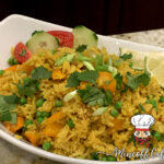 White oval bowl with yellow rice, garnished with lime wedges, cucumber slices, tomato slices, orange bell peppers, chopped green onions and cilantro.