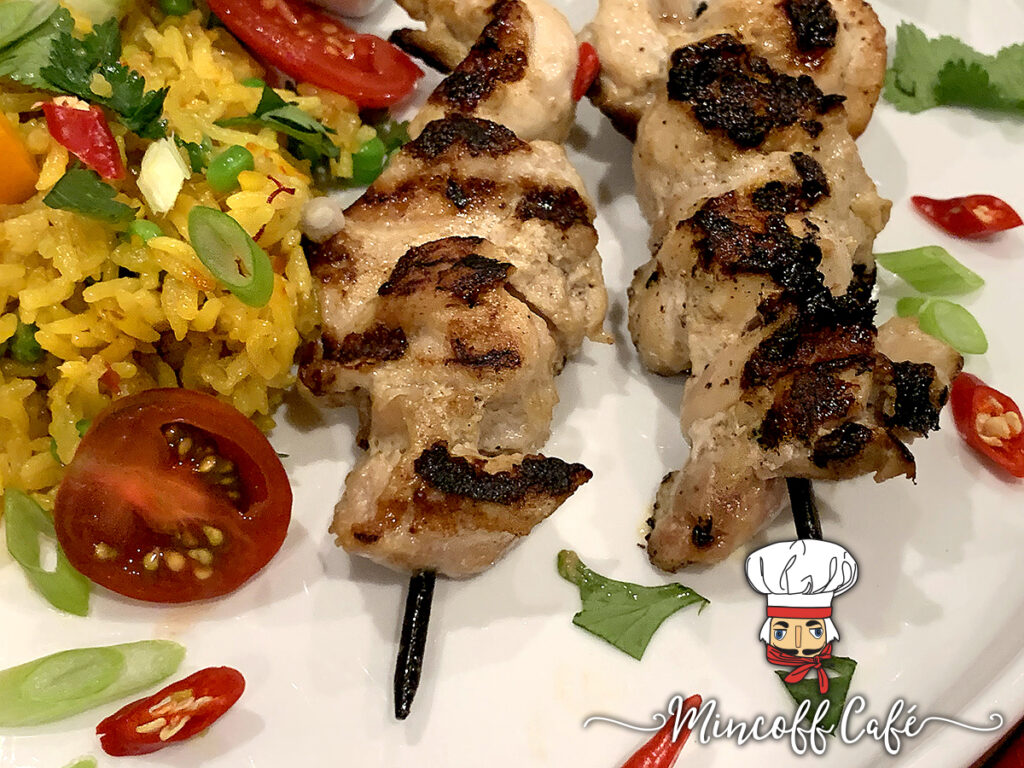 Close up of two skewers of charred, grilled chicken, yellow rice with cucumber, tomato and orange bell pepper slices.