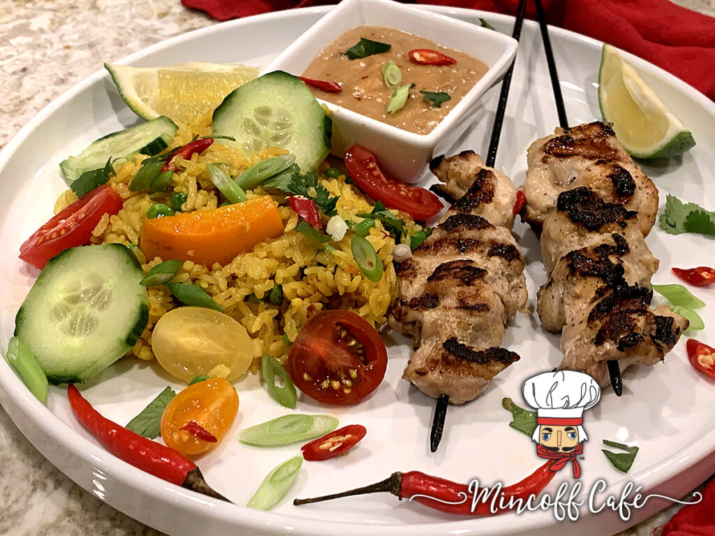 Two skewers of charred, grilled chicken, yellow rice with cucumber, tomato and orange bell pepper slices, on a round white plate along with a tan sauce in a square white ramekin and all garnished with lime wedges, red Thai chilies and cilantro.