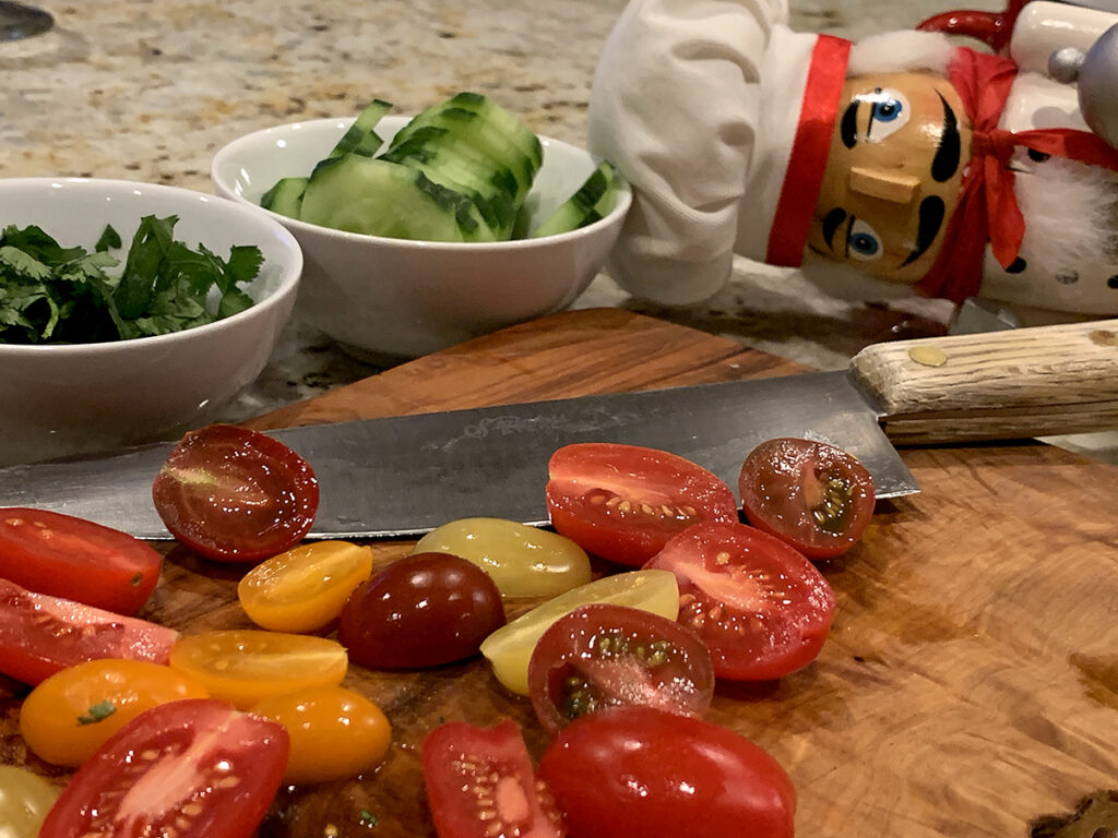 Cherry tomatoes cut in half on a wood cutting board with a chef knife and two small round white bowls filled with cucumber slices and cilantro. There's a nutcracker in the backround who looks like a chef.