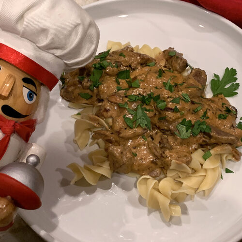 Light brown slightly chunky sauce on top of pale tan wide egg noodles on a white plate. It's sprinkled with green bits of parsley and there's a nutcracker in the foreground that looks like a chef.