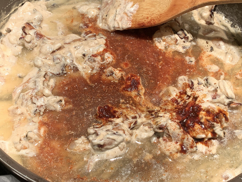 Wooden spoon stirring darker liquids into slightly thick, pale tan and chunky mixture in a skillet.
