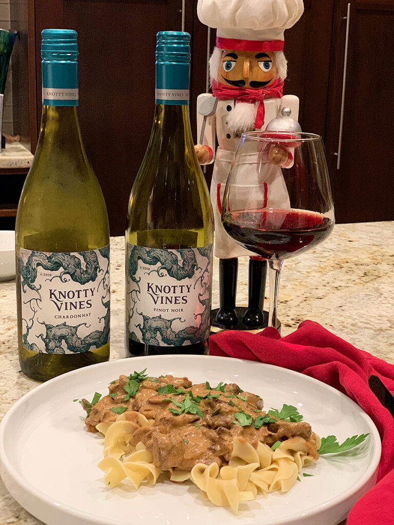 Two wine bottles and a nutcracker who looks like a chef standing behind a tan slightly chunky sauce over wide egg noodles on a round white plate.